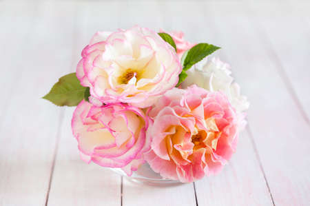 Small bouquet of  Roses on shabby  wooden table.  Selective focus. 免版税图像