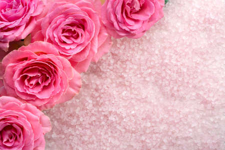 Spa salt crystals and  pink roses.  Flat lay.