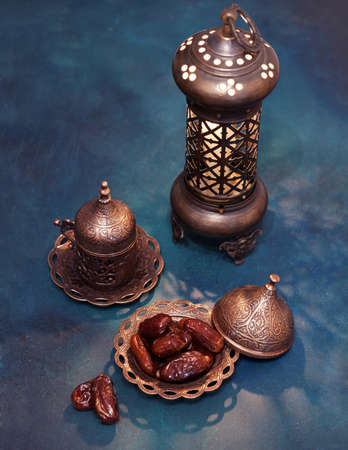 Bronze plate with dates, coffee cup, arabic lantern  on dark blue-green painted  wooden background.  Ramadan background. Toned image 免版税图像