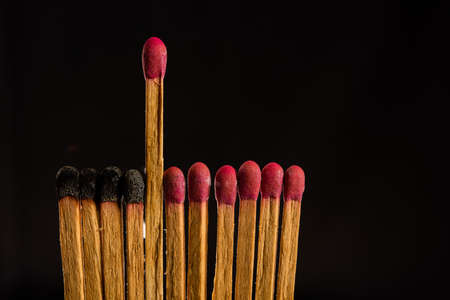 one in the crowd concept of matchstick with flames, with the idea of distance, prominence, dedication and humility, copy space Stock Photo