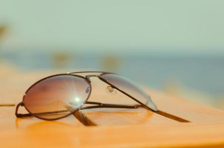 sunglasses on the wood table. Near sea photo