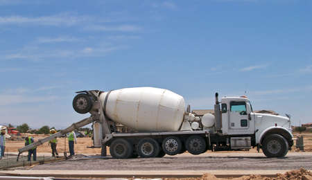 Concrete truck with workers pouring concrete.