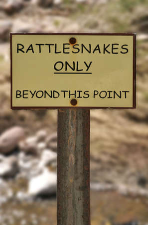 do not enter warning sign: Sign on the trail warns of rattle snakes in a humorous vein.