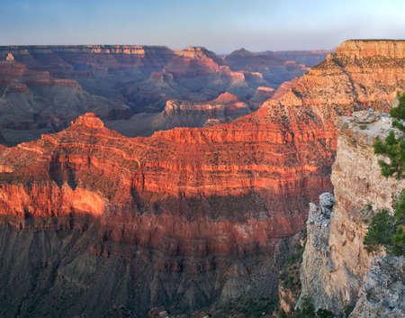 サウスリム、夕日とグランドキャニオンの広大さを楽しむ縁で観光客の夕日 写真素材
