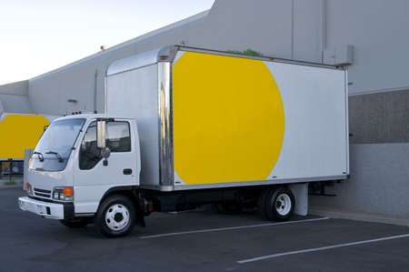White and yellow delivery truck, at loading dock.