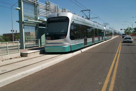 streetcar: Street with streetcar in station and cars.