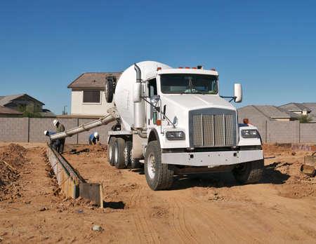 concrete: Concrete mixer pouring concrete at house construction site.