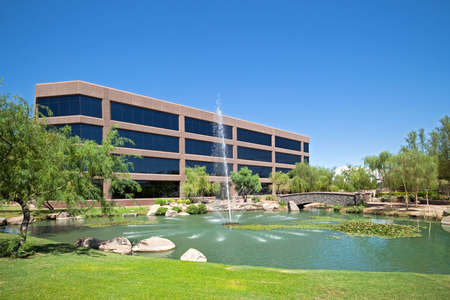 Water fountain in pond in front of an office building.