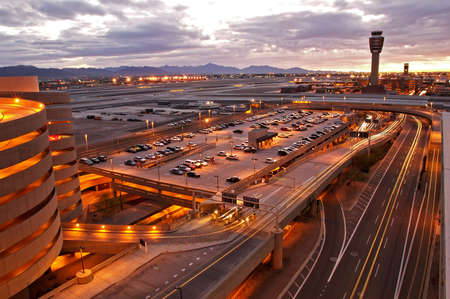 Airport at sunset with lit city skyline. Stock Photo