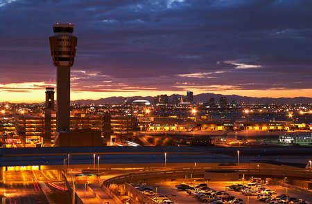 Airport at sunset with lit city skyline. Editorial