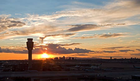 airport runway: Airport at sunset with city skyline.