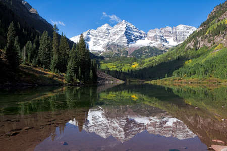 with reflection: Snow covered Maroon Bells in autumn.