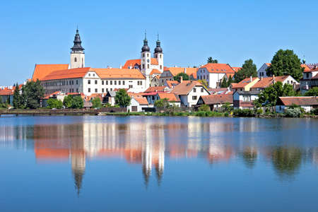 Telc Castle and city reflected in lake.