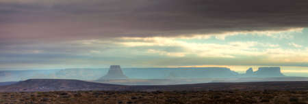 lake powell: Lone Rock in Lake Powell at sunrise under heavy clouds