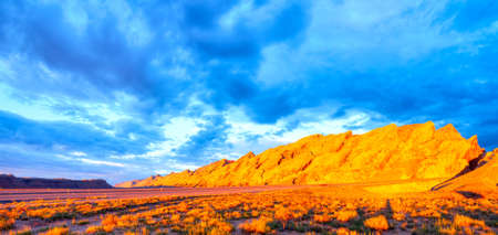 swell: I-70 cut through sunrise lit San Rafael Swell  with storm clouds above
