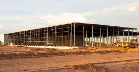 construction machinery: Sunset lit frame of an warehouse under construction  Stock Photo