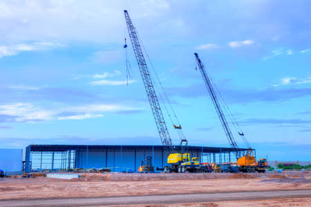 Construction site with big cranes under big sky. Stock Photo