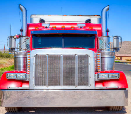 Close up of a red semi truck over a clear blue sky.
