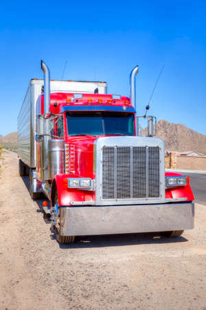 truck driver: Close up of a red semi truck over a clear blue sky.