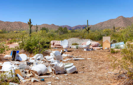 dumped: Garbage dumped on a hillside contrasted with a beautiful, unspoiled landscape in the background. A photo of illegal roadside dumping of trash and garbage.