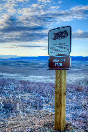 reminding: Sign warning against rattlesnakes, and reminding visitors to   Stay On The Trail