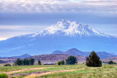 dormant: Mt. Shasta, CA, at sunrise, late spring. A dormant but still active volcano in the Cascades Range, elevation 14,179 feet. Stock Photo