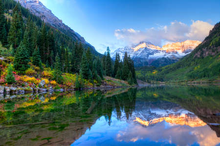 Reflection of Snowcapped Maroon Bells in fall, at sunrise. Banque d'images