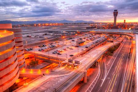 Aeropuerto de Phoenix al atardecer con estelas de luz en la calle. Foto de archivo