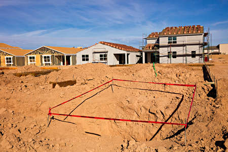 cantieri edili: New homes being constructed on a site.Wooden frame of a new house under construction.