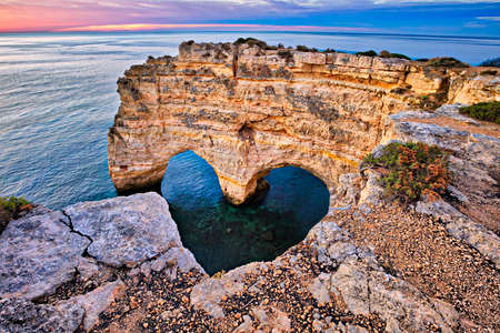 Heart Arch on beautiful coast of Algarve at sunrise, Portugal. Stock Photo