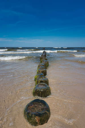 Timbers on the beach in Germany on the island of Usedom ,, wooden groynes on the beach of the island of Usedom