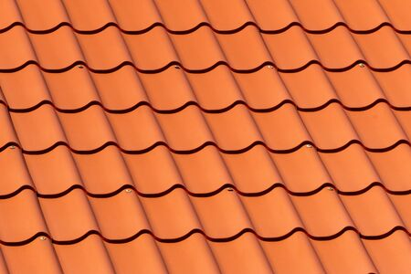 Overlapping rows of red tile roofing in Estonia, ridge tiling material pattern in horizontal orientation.