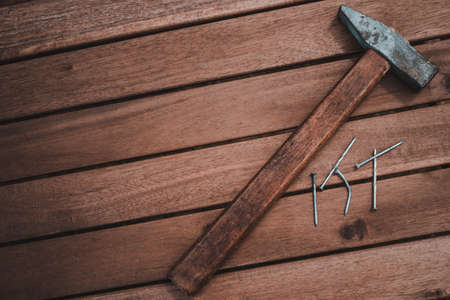 The old carpenter hammer to hit the nails on the wooden table. Wood background Imagens