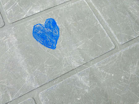 A blue heart clumsily drawn in chalk by a child's hand on a gray-green surface of an old scratched table