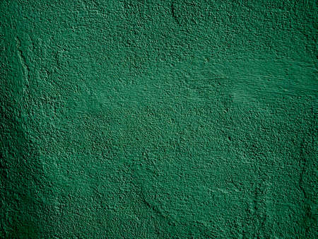Green concrete wall is a decorative or textured surface. Can be used as a background or for design purposes