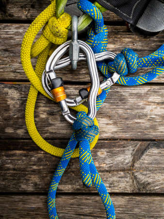 Used climbing equipment on the wooden background- carabiners with small scratches with blue and yellow ropes Banque d'images