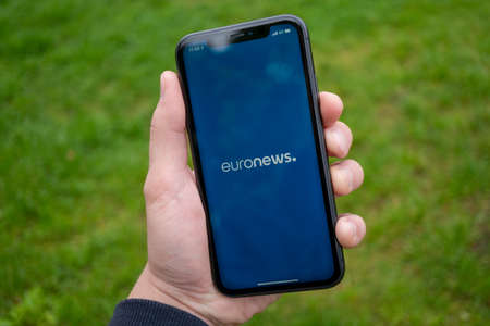 Tallinn / Estonia - September 1, 2020: Black iPhone with logo of news media EuroNews on the screen. News media icon. Business suit on the background