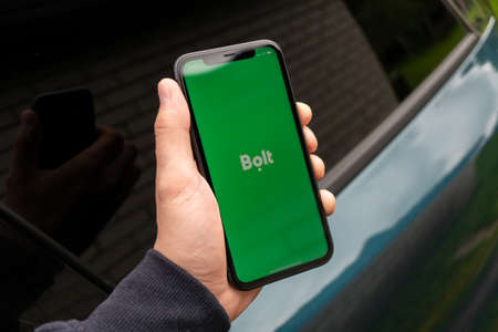Tallinn / Estonia - September 1, 2020: Black iphone with logo of Bolt application on the screen. Hand with phone. Can be used as illustrative for marketing or business concept