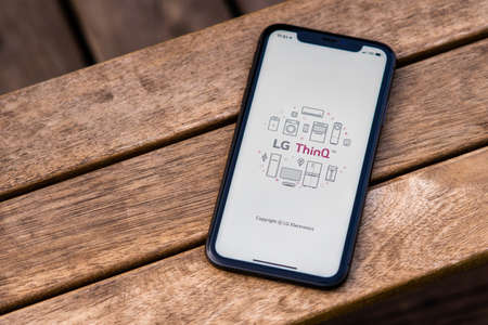 Tallinn / Estonia - September 28, 2020: Black iphone with logo of LG ThinQ app on the screen. Wooden background. Can be used as illustrative for marketing or business concept