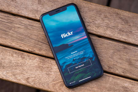 Tallinn / Estonia - September 28, 2020: Black iphone with logo of Social media Flickr on the screen. Wooden background. Can be used as illustrative for marketing or business concept