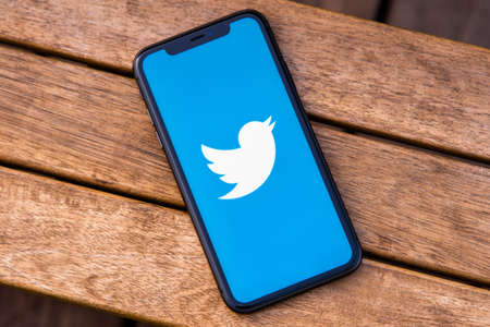 Tallinn / Estonia - September 28, 2020: Black iphone with logo of social media Twitter on the screen. Wooden background. Can be used as illustrative for marketing or business concept