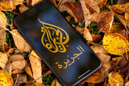 Tallinn / Estonia - September 28, 2020: Black iphone with logo of news media Al Jazeera on the screen. Falled leaves background. Can be used as illustrative for marketing or business concept Éditoriale