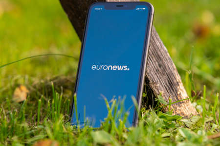 Tallinn / Estonia - September 28, 2020: Black iphone with logo of news media EuroNews on the screen. Green grass background. Can be used as illustrative for marketing or business concept