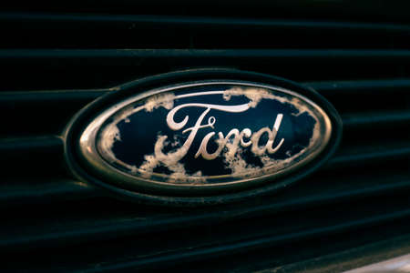 Tallinn / Estonia - Mai 1, 2021: Close up of old and damaged Ford emblem on the grill. Economy class car accessories and design elements. Close-up image. American car