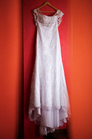 White wedding dress on the red wall