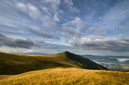 high dynamic range: Fresh and ethereal mountains landscape with yellow grass and cloudy dynamic sky