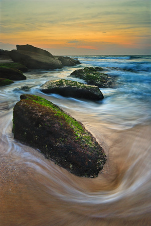 Sunrise seascape with a lone mossy rock with a flowing wave around it Reklamní fotografie