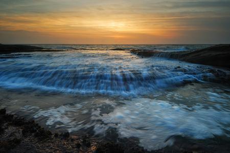 Sunrise seascape with rushing waves photo