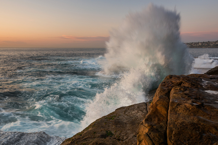unrest: Sunrise seascape with unrest sea and blue water and with sky lit orange rocks and big crashing wave Stock Photo