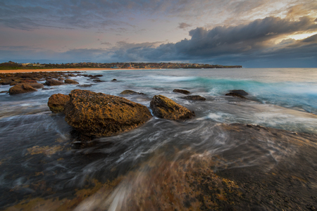 large rocks: Seascape sunrise long exposure with flowing water around large rocks and light pink and blue sky Stock Photo